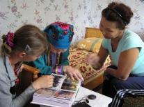 Татьяна Ивановна Торпушонок, Неля Якимовна Елкина и Женя Ренковская рассматривают старые фотографии